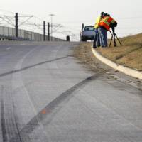 Photo - Tire skid marks are seen leaving the road as news cameraman film the area where a single vehicle accident involving Dallas Cowboys player Josh Brent occurred Saturday, Dec. 8, 2012, in Irving, Texas. Brent is facing an intoxication manslaughter charge after a one-vehicle accident that killed linebacker Jerry Brown, a member of the team's practice squad. (AP Photo/Tony Gutierrez)