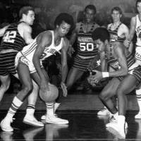 Photo - FILE - In this March 21, 1970, file photo, Marquette's Dean Meminger, right, attempts to take the ball from St. John's Richard Gilkes, front left, during a National Invitational Tournament basketball game at New York's Madison Square Garden. Meminger, who played a reserve role on the New York Knicks' 1973 NBA championship team, was found dead Friday, Aug. 23, 2013, in a New York hotel room. He was 65. (AP Photo/Marty Lederhandler, File)