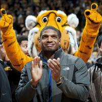 Photo - FILE - In this Feb. 15, 2014, file photo, Missouri's All-American defensive end Michael Sam claps during the Cotton Bowl trophy presentation at halftime of an NCAA college basketball game between Missouri and Tennessee in Columbia, Mo. Sam was selected in the seventh round, 249th overall, by the St. Louis Rams in the NFL draft Saturday, May 10, 2014. The Southeastern Conference defensive player of the year last season for Missouri came out as gay in media interviews this year.   (AP Photo/L.G. Patterson, File)