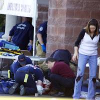 Photo - FILE - Emergency personnel attend to a shooting victim  outside a shopping center in Tucson, Ariz. in this Saturday, Jan. 8, 2011 file photo taken where U.S. Rep. Gabrielle Giffords, D-Ariz., and others were shot as the congresswoman was meeting with constituents. Hundreds of pages of police reports in the investigation of the Tucson shooting rampage that wounded former Rep. Gabrielle Giffords are being released Wednesday, March 27, 2013 marking the public's first glimpse into documents that authorities have kept private since the attack more than two years ago.  (AP Photo/James Palka, File)