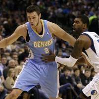 Photo - Denver Nuggets small forward Danilo Gallinari (8), of Italy, gets by Dallas Mavericks' O.J. Mayo (32) on a drive to the basket in the first half of an NBA basketball game on Friday, Dec. 28, 2012, in Dallas. (AP Photo/Tony Gutierrez)