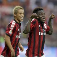 Photo - AC Milan midfielder Sulley Muntari, of Ghana, right, celebrates flanked by his teammate forward Keisuke Honda after scoring his side's second goal, during a Serie A soccer match between AC Milan and Lazio, at the San Siro stadium in Milan, Italy, Sunday, Aug. 31, 2014. (AP Photo/Luca Bruno)