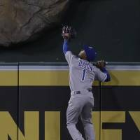 Photo - Kansas City Royals center fielder Jarrod Dyson can't get a glove on a home run by Los Angeles Angels' Mike Trout during the eighth inning of a baseball game in Anaheim, Calif., Wednesday, May 15, 2013. Dyson was hurt on the play. (AP Photo/Chris Carlson)