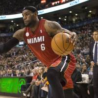 Photo - Miami Heat's LeBron James drives at the Toronto Raptors' defence as Heat's Head Coach Erik Spoelstra looks on during first half NBA basketball action in Toronto on Sunday, March 17, 2013.  (AP Photo/The Canadian Press, Chris Young)
