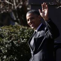 Photo - President Barack Obama waves to reporters as they shout questions to him regarding the fiscal cliff as he walks across Pennsylvania Avenue back to the White House in Washington, Thursday, Dec. 13, 2012. Obama had dropped by a holiday party for the National Security Council at Blair House. (AP Photo/Charles Dharapak)