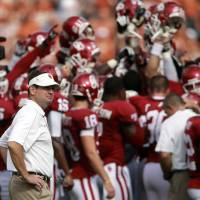 Photo - FILE - In this Oct. 13, 2012, file photo, Oklahoma head coach Bob Stoops looks on as his team huddles up before an NCAA college football game against Texas at the Cotton Bowl in Dallas. After a blowout loss in the Cotton Bowl, Oklahoma faces a major overhaul this offseason.  (AP Photo/Michael Mulvey, File)