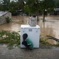 Photo -   A boy tries to take cover from the cold behind an appliance sitting higher than the floodwaters triggered by Tropical Storm Isaac in Port-au-Prince, Haiti, Saturday Aug. 25, 2012. Tropical Storm Isaac swept across Haiti's southern peninsula early Saturday, dousing a capital city prone to flooding and adding to the misery of a poor nation still trying to recover from the 2010 earthquake. (AP Photo/Dieu Nalio Chery)