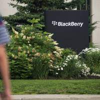 Photo - FILE- In this Tuesday, July 9, 2013, file photo, pedestrians walk near BlackBerry's headquarters in Waterloo, Ontario, on the morning of the company's Annual General Meeting. BlackBerry said Friday, Sept. 20, 2013,  it will lay off 4,500 employees, or 40 percent of its global workforce, and is announcing a nearly $1 billion second-quarter loss in a surprise early release of earnings.  (AP Photo/The Canadian Press,  Geoff Robins, File)