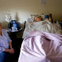 Photo - BJ Matthews waits by the bed of her husband, Bob Matthews, as he continues to recover from the effects of West Nile Virus in Oklahoma City, Friday, August 10, 2012. Photo by Bryan Terry, The Oklahoman