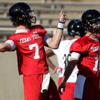 Photo - In this photo from Aug. 3, 2013, Texas Tech's Davis Webb(7) and Michael Brewer(16) throw passes during their NCAA college football practice in Lubbock, Texas. (AP Photo/Lubbock Avalanche-Journal, Stephen Spillman)
