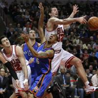 Photo - Chicago Bulls center Brad Miller, right, blocks the shot of Oklahoma City Thunder guard Eric Maynor (6), as Kirk Hinrich, left, and Nick Collison watch during the first half of an NBA basketball game Monday, Jan. 4, 2010, in Chicago. (AP Photo/Charles Rex Arbogast)