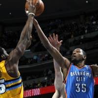 Photo - Denver Nuggets forward Kenneth Faried, left, reaches to block a shot by Oklahoma City Thunder forward Kevin Durant in the first quarter of an NBA basketball game in Denver on Sunday, Jan. 20, 2013. (AP Photo/David Zalubowski)