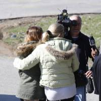 Photo - A pair of women walk arm-in-arm off the campus of the Franklin Regional School District, where several people were stabbed at Franklin Regional High School on Wednesday, April 9, 2014, in Murrysville, Pa., near Pittsburgh. The suspect, a male student, was taken into custody and being questioned. (AP Photo/Keith Srakocic)