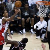 Photo - Toronto Raptors guard DeMar DeRozan, left, drives over Brooklyn Nets forward Andray Blatche to score during the second half of Game 2 in an NBA basketball first-round playoff series, Tuesday, April 22, 2014, in Toronto. (AP Photo/The Canadian Press, Nathan Denette)