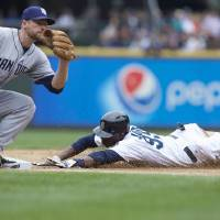 Photo - Seattle Mariners' James Jones steals third base as San Diego Padres third baseman Chase Headley attempts to make a tag during the fifth inning of a baseball game in Seattle, Tuesday, June 17, 2014. (AP Photo/Stephen Brashear)