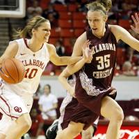 Photo - OU's Morgan Hook (10) drives past Roz Hamilton (35) of Oklahoma Christian during a women's college basketball exhibition game between the University of Oklahoma and Oklahoma Christian University at the Lloyd Noble Center in Norman, Okla., Thursday, Nov. 1, 2012. Photo by Nate Billings, The Oklahoman