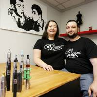 Photo - Stephanie and John Durst pose with some of their more elaborate e-cigarette products in the OKC Vapes store located on 3710 NW 50th St. in Oklahoma City. Photo by Aliki Dyer,  The Oklahoman  Aliki Dyer - The Oklahoman