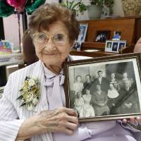 Photo - Sister Mary Clotilda Toelle holds a photo of her and her family Wednesday at The Mercy Convent.