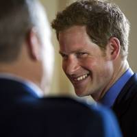 Photo - Britain's Prince Harry greets attendees before a reception in the Prince's honor at the Ambassador's residence in Washington, Thursday, May 9, 2013. (AP Photo/Jim Lo Scalzo, Pool)