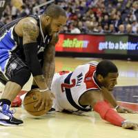 Photo - Orlando Magic guard Jameer Nelson (14) grabs the loose ball in front of Washington Wizards guard John Wall (2) in the first half of an NBA basketball game Monday, Jan. 14, 2013 in Washington. (AP Photo/Alex Brandon)