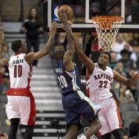 Photo - Memphis Grizzlies' Quincy Pondexter, center, tries to shoot with Toronto Raptors' DeMar DeRozan (10) and Rudy Gay (22) defending during the first half of a preseason NBA basketball game in Toronto on Wednesday, Oct. 23, 2013. (AP Photo/The Canadian Press, Frank Gunn)