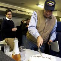 Photo - The traveling staff on board the E-4B surprise U.S. Defense Secretary Leon Panetta with a cake that says