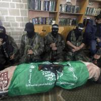 Photo - Masked Hamas militants knell next to the flagged-draped body of Hamas member of the Palestinian Parliament Mariam Farhat, 64, who died early Sunday at the Gaza hospital in Gaza City, Sunday, March 17, 2013. Farhat, known as the