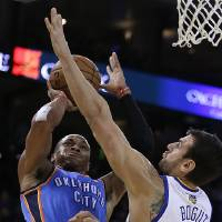 Photo - Oklahoma City Thunder's Russell Westbrook, left, shoots against Golden State Warriors' Andrew Bogut (12) during the first half of an NBA basketball game Thursday, Nov. 14, 2013, in Oakland, Calif. (AP Photo/Ben Margot)