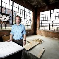 Photo - Architect Brian Fitzsimmons looks over plans for the Guardian Apartments. Photo by Steve Gooch, The Oklahoman