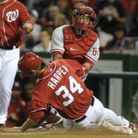 Photo -   Washington Nationals' baserunner Bryce Harper steals home as Philadelphia Phillies catcher Carlos Ruiz applies a late tag during first inning of their baseball game at Nationals Park, Sunday, May 6, 2012, in Washington. Harper was on third base went he scored to give the Nationals a 1-0 lead. (AP Photo/Richard Lipski)