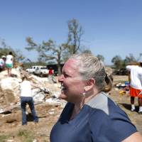 Photo - Kristina Miller watches volunteers, including Oklahoma State players, clear her destroyed home from her property, Wednesday, June 12, 2013, in Bethel Acres, Okla. Photo by Sarah Phipps, The Oklahoman