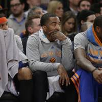 Photo - New York Knicks' Carmelo Anthony, left, J.R. Smith, center, and Amar'e Stoudemire, right, watch their team play during the first half of an NBA basketball game against the Philadelphia 76ers Monday, March 10, 2014, in New York. (AP Photo/Frank Franklin II)