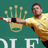Photo - Stanislas Wawrinka of Switzerland, returns to the ball to Milos Raonic of Canada during their quarterfinals match of the Monte Carlo Tennis Masters tournament in Monaco, Friday, April 18, 2014. Wawrinka won 7-6 6-2. (AP Photo/Michel Euler)