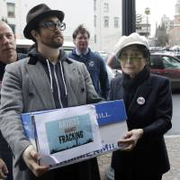 Photo - Sean Lennon and Yoko Ono help deliver boxes of comments to the New York State Department of Environmental Conservation on its proposed natural gas drilling regulations on Friday, Jan. 11, 2013, in Albany, N.Y. Environmental, health and community groups opposed to shale gas drilling and hydraulic fracturing, or
