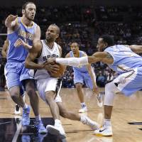 Photo - San Antonio Spurs' Tony Parker, center, of France, drives between Denver Nuggets defenders Kosta Koufos (41) and Andre Iguodala (9) during the first half of an NBA basketball game, Wednesday, March 27, 2013, in San Antonio. (AP Photo/Eric Gay)