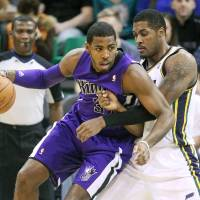 Photo - Utah Jazz's Derrick Favors, right, defends against Sacramento Kings' Jason Thompson, left, as he makes a drive in the first half of an NBA basketball game Monday, Jan. 27, 2014, in Salt Lake City. (AP Photo/Rick Bowmer)