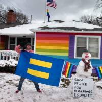 Photo -  Aaron Jackson, who runs the nonprofit group Planting Peace, recently bought the house across the street from Westboro Baptist Church and painted it all the colors of the rainbow in protest of the church's ideology.
