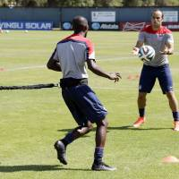 Photo - United States' Landon Donovan, right, and DaMarcus Beasley take part in drills during training in preparation for the World Cup soccer tournament on Wednesday, May 21, 2014, in Stanford, Calif. (AP Photo/Marcio Jose Sanchez)