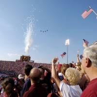Photo - Norman, Oklahoma - September 11, 2004. University of Oklahoma against Houston college football game at The Gaylord Family - Oklahoma Memorial Stadium.   U.S., UNITED STATES, TERRORISM, TERRORIST ATTACKS, ANNIVERSARY: Oklahoma Sooners fans wave flags as Air Force T-38's fly overhead at The Gaylord Family - Oklahoman Memorial Stadium in honor of the victims of 9/11 prior to the OU-Houston game Saturday. Staff photo by Bryan Terry