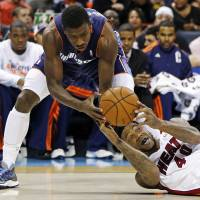Photo - Miami Heat's Udonis Haslem, bottom, looks to pass as Charlotte Bobcats' Michael Kidd-Gilchrist, top, defends during the first half of an NBA basketball game in Charlotte, N.C., Wednesday, Dec. 26, 2012. (AP Photo/Chuck Burton)