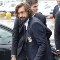 Photo - Italy soccer player Andrea Pirlo carries his luggage upon his arrival with his teammates at Malpensa airport after landing from Brazil, in Milan, Italy, Thursday, June 26, 2014. Italy was disqualified from the World Cup after loosing to Uruguay in their group stage round. Pirlo recently quit the national team. Pirlo had said before the tournament he would quit international football after Brazil. (AP Photo/Luca Bruno)