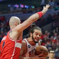 Photo - Chicago Bulls center Joakim Noah drives on Washington Wizards center Marcin Gortat during Game 5 of an NBA basketball first-round playoff series, Tuesday, April 29, 2014, in Chicago. The Wizards won 75-69, taking the series. (AP Photo/Daily Herald, Steve Lundy) MANDATORY CREDIT  MAGS OUT