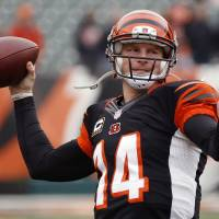 Photo - FILE - In this Dec. 29, 2013 file photo, Cincinnati Bengals quarterback Andy Dalton warms up prior to an NFL football game against the Baltimore Ravens, in Cincinnati. Dalton is comparing himself with some of the NFL's top quarterbacks while negotiating a contract extension with the Bengals. He knows the one stat that's holding him back: 0-3 in the postseason. (AP Photo/David Kohl, File)