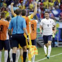Photo - France's Olivier Giroud, second from right, celebrates after scoring the opening goal during the group E World Cup soccer match between Switzerland and France at the Arena Fonte Nova in Salvador, Brazil, Friday, June 20, 2014.  (AP Photo/Christophe Ena)