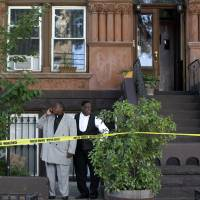Photo - Bishops Gerald Seabrooks, right, and Willie Billips stand in front of the home of Cathleen Alexis, mother of Washington Navy Yard gunman Aaron Alexis, who made a statement at her home in New York's Brooklyn borough on Wednesday, Sept. 18, 2013. The bishops are part of a Brooklyn Clergy-NYPD Task Force. Cathleen Alexis said that she does not know why her son did what he did and she will never be able to ask him. Aaron Alexis opened fire Monday, killing 12 people, before he was killed in a shootout with police. (AP Photo/Seth Wenig)