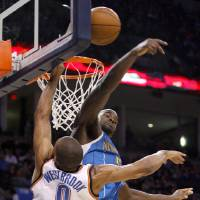 Photo - Emeka Okafor of New Orleans blocks the shot of Oklahoma City's Russell Westbrook during the NBA basketball game between the Oklahoma City Thunder and the New Orleans Hornets at the Ford Center in Oklahoma City, Wednesday, January 6, 2009. Photo by Bryan Terry, The Oklahoman ORG XMIT: KOD