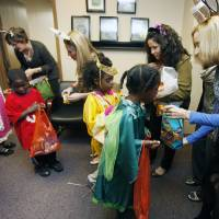 Photo - Positive Tomorrows kids Ayana, left, Tony, LeRuby, and Myia trick or treat through the offices of the Oklahoma Medical Research Foundation. By Paul Hellstern, The Oklahoman  PAUL HELLSTERN - Oklahoman