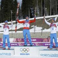 Photo - Russia's gold medal winner Alexander Legkov is flanked by Russia's silver medal winner Maxim Vylegzhanin, left and Russia's bronze medal winner Ilia Chernousov during the flower ceremony of the men's 50K cross-country race at the 2014 Winter Olympics, Sunday, Feb. 23, 2014, in Krasnaya Polyana, Russia. (AP Photo/Gregorio Borgia)