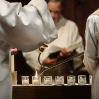 Photo - At St. Paul's Episcopal Cathedral in Oklahoma City, 28 small white candles are lit at the beginning of a service remembering those who died as a result of a Connecticut shooting massacre. Photo by Jim Beckel, The Oklahoman