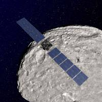 Photo -   An undated artist rendering released by NASA shows the NASA Dawn spacecraft in orbit around the giant asteroid Vesta. After spending a year examining Vesta, Dawn is poised to depart and head to another asteroid, Ceres, where it will arrive in 2015.(AP Photo/NASA)
